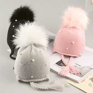 Pink baby girl's beanie hat with pearls and pom pom